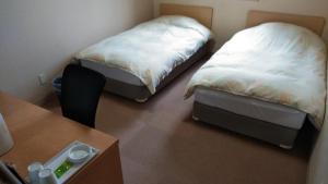 OYO Hotel Hachi No Oyado Numadate Heights Akita客房内的一张或多张床位