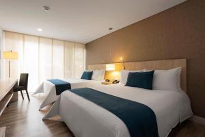 BH比森特纳里奥酒店客房内的一张或多张床位