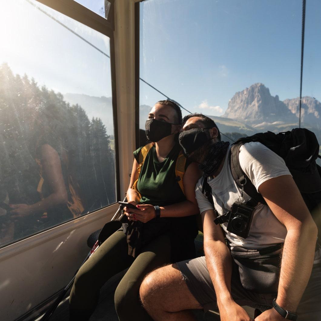 一对情侣戴着口罩,乘坐缆车越过群山