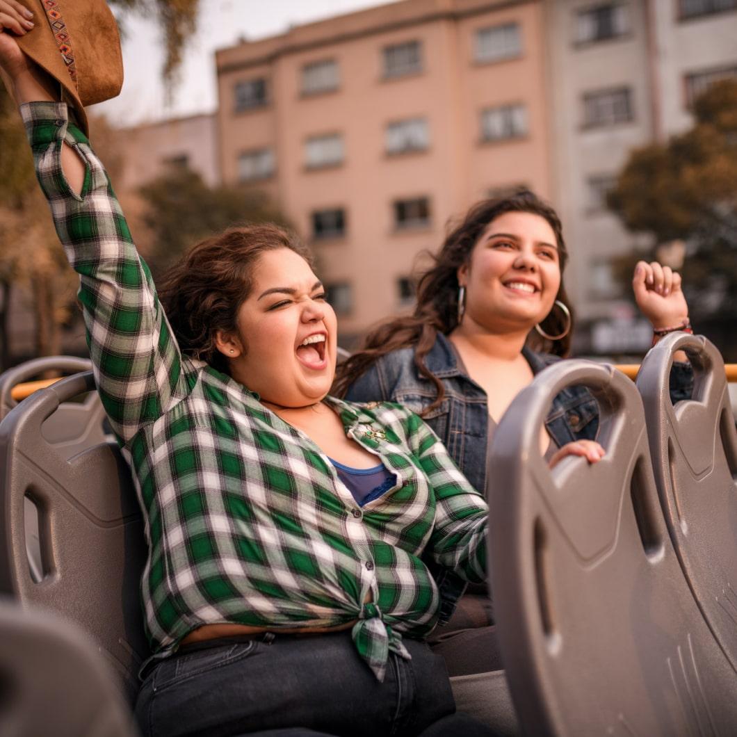 两名旅客坐在双层巴士的顶层,看着非常开心